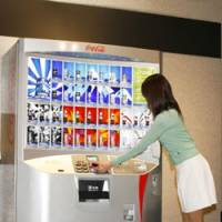Cashless purchase: A woman uses a cell phone with an electronic-money function to buy a beverage from a vending machine.   COURTESY OF COCA-COLA (JAPAN) CO.