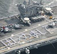 Greetings: Crew members form the word 'Hajimemashite' ('Nice to meet you') on the flight deck of the USS George Washington as it heads into the U.S. naval base in Yokosuka, Kanagawa Prefecture, on Thursday morning. | KYODO PHOTO