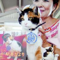 On duty: Tama the 'stationmaster' cat poses with a photo book featuring herself at Kishi Station on the Kishigawa Line in Wakayama Prefecture in September. | KYODO PHOTO