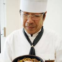Food for thought: Hiroshi Tsuchikiri, a chef at an eatery in the National Diet Library in the Nagata-cho district of Tokyo, holds up a symbolically divided 'Diet Rice Bowl' meal in this recent file photo. | KYODO PHOTO