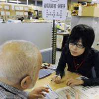 Future in doubt: An elderly man consults a social security official about his pension in Taito Ward, Tokyo, on Wednesday, when medical insurance premiums for about 6.69 million people aged 75 and over were automatically deducted from their benefits. | KYODO PHOTO