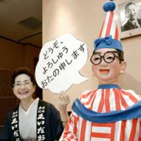 New shtick: Michiko Kakinoki, owner of famed Osaka eatery mannequin Kuidaore Taro, holds up a sign in the local dialect reading 'Please remember me' as she tells reporters Monday the doll will now be used for promotional purposes.   KYODO PHOTO