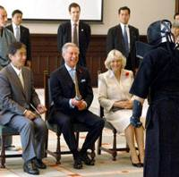Britain's Prince Charles smiles while holding a bamboo kendo sword Tuesday at Keio University in Tokyo as his wife, Camilla, looks on. The couple, on a five-day visit, viewed a kendo match and other performances of traditional Japanese culture. | YOSHIAKI MIURA PHOTO