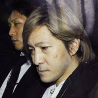 Grim-faced: Music producer Tetsuya Komuro is taken to the Osaka prosecutor's office Tuesday morning. | KYODO PHOTO