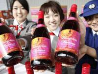 Ready to pop: Workers at Narita airport show off bottles of this year's batch of Beaujolais Nouveau wine in Narita, Chiba Prefecture, on Friday. | KYODO PHOTO