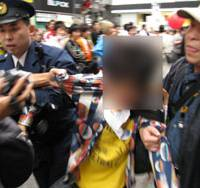 Walk this way: Police arrest a man taking part in an organized walk to view Prime Minister Taro Aso's Shibuya Ward, Tokyo, home on Oct. 26. | COURTESY OF PART-TIMER, ARBEITER, FREETER & FOREIGN WORKERS