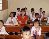 Class act: Erin Keown Ganju, who will take over as CEO of Room to Read next year, poses with students in Kien Giang Province, Vietnam, in 2002. | COURTESY OF ERIN KEOWN GANJU