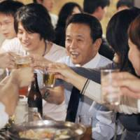 Here's to better approval ratings: Prime Minister Taro Aso raises his glass in a toast with college students during a party at a Tokyo pub Sunday night. | KYODO PHOTO