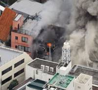 Still smoldering: Smoke escapes from buildings set on fire by a series of explosions that took place Wednesday in Shibuya Ward, Tokyo. | KYODO PHOTO