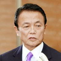 In the hot seat: Prime Minister Taro Aso fields questions from reporters last week at the prime minister's office. | KYODO PHOTO