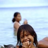 Island girl: Fatogea Matagale eats fresh fish just caught in the sea of Funafuti Island in April 2007. She told photographer Shuichi Endo, 'I am happy whenever I play a kick-the-can game with my friends. I wish to make more friends.' | COURTESY OF SHUUICHI ENDOU