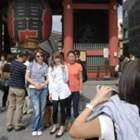 Snapshot: Visitors get their picture taken in front of Sensoji Temple, a popular tourist spot in Taito Ward, Tokyo. | YOSHIAKI MIURA PHOTO