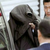 Suspect: Police put Dang Xuan Hop into a car at Fukuoka airport Wednesday. | KYODO PHOTO