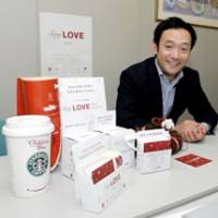 Helping others: Daigo Sato, head of Charity Platform, displays collection boxes Wednesday for the Say LOVE charity campaign during an interview in Tokyo. | YOSHIAKI MIURA PHOTO