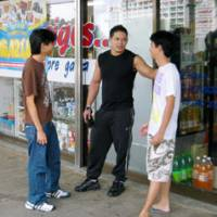 On the street: Chago Iwasa, a third-generation Japanese-Brazilian (center) hangs out with friends in front of a Brazilian food store in Toyota, Aichi Prefecture, in October. Iwasa lost his job at an auto parts company. | KYODO PHOTO