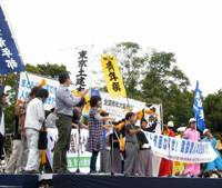 On the firing line: Young temp workers gather to protest their plight in Meiji Park in Shibuya Ward, Tokyo, in October. Among the many banners is one that reads: 'Eliminate poverty and disparity.'   NATSUKO FUKUE