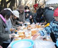 A helping hand: Volunteers prepare sandwiches Wednesday at Tokyo's Hibiya Park for temp workers who have lost their jobs. The event runs through Monday. | SATOKO KAWSAKI PHOTO
