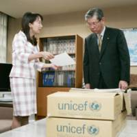 Taking action: Agnes Chan, singer and goodwill ambassador for UNICEF, submits a petition demanding a tighter ban on child pornography to LDP Policy Research Council Chairman Kosuke Hori at LDP headquarters in Tokyo on Tuesday.   KYODO PHOTO