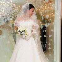 Goin' to the chapel: A woman tries on her wedding dress before her marriage. Experts urge Japanese women to engage in 'marriage hunting' to maximize their chances of meeting 'Mr. Right.' | SATOKO KAWSAKI PHOTO