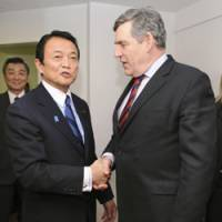 So what's the plan?: Prime Minister Taro Aso shakes hands with British Prime Minister Gordon Brown in Davos, Switzerland, on Saturday. | KYODO PHOTO