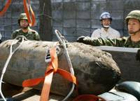 Members of the Japanese Ground Self-Defense Force load a 250-kg dud bomb after it was defused Sunday at Miyazaki Airport. The unexploded bomb was discovered Jan. 24.   KYODO PHOTO