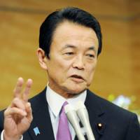 Keep us posted: Prime Minister Taro Aso answers a reporter's question about postal reform Tuesday. | KYODO PHOTO