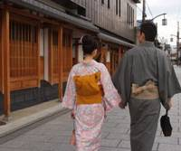 Back street: A young couple stroll by 'machiya' wooden town houses in Kyoto's traditional weaving district of Nishijin. The traditional houses are a key component of the city's attempts to build a viable eco-tourism and slow food, slow life tourist industry. | THE KYOTO TOURISM COUNCIL