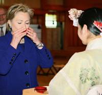 Local color: U.S. Secretary of State Hillary Rodham Clinton takes a sip of 'sacred sake' in a ceremony at Meiji Shrine in Tokyo on Tuesday ahead of talks with top officials. | KYODO PHOTO