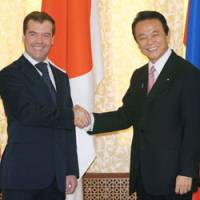 Conflict resolution: Russian President Dmitry Medvedev poses with Prime Minister Taro Aso in Yuzhno-Sakhalinsk, Russia, on Wednesday morning. | KYODO PHOTO