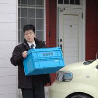 Eely feeling: A police investigator carries a box of items seized Thursday from the home of Shuto Oyama, former president of Sunrise Foods in Matsuyama, Ehime Prefecture. | KYODO PHOTO