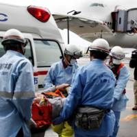 Terra firma: A Northwest Airlines passenger injured by turbulence is put into an ambulance Friday at Narita airport in Chiba Prefecture. The accident injured 43 on board.   KYODO PHOTO