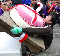 Sweet taste of victory: A participant in a contest of strength holds up a 150-kg 'mochi' pounded-rice cake at Kyoto's Daigoji Temple Monday.   KYODO PHOTO