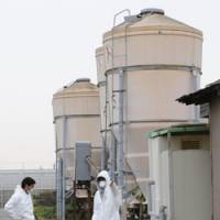 For the birds: Workers in hazard suits disinfect a quail farm where a bird-flu outbreak was reported in Toyohashi, Aichi Prefecture, on Friday. | KYODO PHOTO