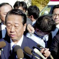 That was then: Democratic Party of Japan President Ichiro Ozawa speaks to reporters as his chief secretary, Takanori Okubo (upper right), looks on in this file photo taken last June in Ichinoseki, Iwate Prefecture. | KYODO PHOTO
