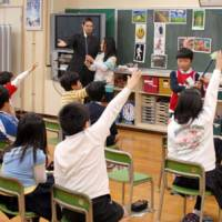 Pick me, me, me: Fourth graders vie for turns to play a picture game with visiting American instructor Sam West during an English class at Shiba Public Elementary School in Minato Ward, Tokyo, as homeroom teachers Minako Sugawa (right) and  Katsuhiko Kaneko (left) help out. | YOSHIAKI MIURA PHOTO
