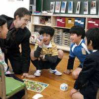 All on board: Fourth-graders play a board game during an English class with visiting American instructor Sam West in the World Room at Shiba Public Elementary School in Minato Ward, Tokyo, on Feb. 23. | YOSHIAKI MIURA PHOTO
