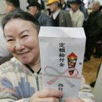 The envelope please: A woman holds up an envelope containing her cash handout Thursday at the municipal office in Nishimeya, Aomori Prefecture, one of two towns that began disbursing the money after the supplementary budget for 2009 cleared the Diet on Wednesday.   KYODO PHOTO