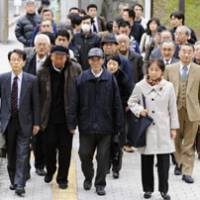 Hopes dashed: Chinese plaintiffs in a suit over wartime forced labor enter the Fukuoka High Court on Monday. | KYODO PHOTO