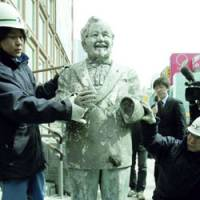 Resurrected: A construction worker supports a statue of Kentucky Fried Chicken founder Colonel Sanders on Wednesday after reassembling it with parts discovered in Osaka's Dotonbori River the previous day. | KYODO PHOTO