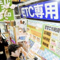 Gotta pay to save: A customer checks out an electronic toll collection system device Thursday at a car products store in Koto Ward, Tokyo.   KYODO PHOTO
