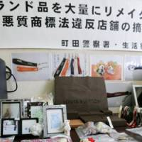Fancy stash: Confiscated products remade from luxury brand products are shown Tuesday at Machida Police Station in Tokyo.   KYODO PHOTO