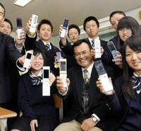 Learning tool: Students at Kochi Chuo High School and Principal Katsuji Kusui show off their cell phones Thursday.   KYODO PHOTO