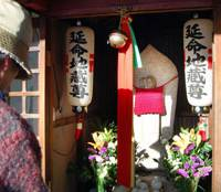 For good fortune: A visitor prays in front of an Enmei Jizo statue in the city of Wakayama where 40 million was found Feb. 20. | KYODO PHOTO