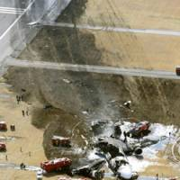 An aerial photo shows the wreckage of Flight 80, a FedEx cargo plane that crash-landed at 6:50 a.m. Monday morning at Narita International Airport. | KYODO PHOTO