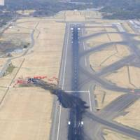 Deadly path: A burn scar on the runway at Narita International Airport shows the path a FedEx cargo jet took when it crashed Monday morning.   KYODO PHOTO