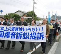 Sounding off: Plaintiffs in a damages suit against the government over noise from the U.S. Marine Corps Air Station Iwakuni in Yamaguchi Prefecture march Monday in Iwakuni with supporters holding a banner saying 'We don't want any more noise from military aircraft.' | KYODO PHOTO