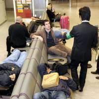 Holding pattern: Stranded travelers lie on benches early Tuesday in a passenger terminal at Narita International Airport after a FedEx cargo plane crash the previous day disrupted flights. | KYODO PHOTO