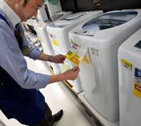 Priced to move: A store clerk checks the information on a made-in-China Haier washing machine at a Seiyu outlet in Tokyo.   AP PHOTO