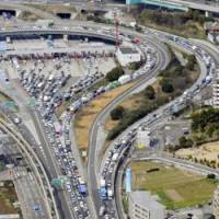 The Suita Interchange on the Meishin Expressway is jammed with traffic Saturday as a cheaper system of expressway tolls took effect. | KYODO PHOTO