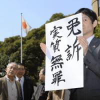 No consolation: A supporter for a man and woman seeking to overturn the conviction of their father in the 1945 Yokohama Incident holds up a sign Monday outside the court saying the retrial was dismissed. | KYODO PHOTO